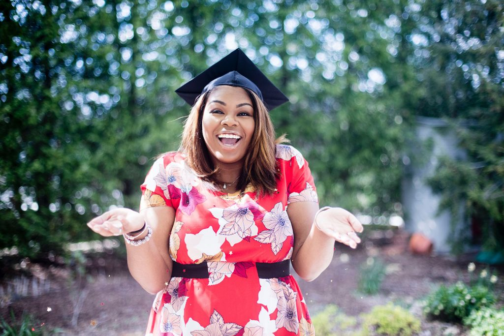 A happy college graduate who successfully transferred colleges to receive the highest education she could before entering the workforce.